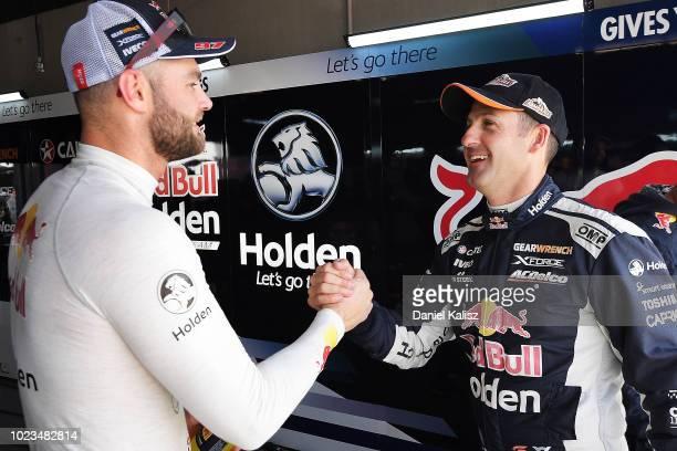 Shane Van Gisbergen driver of the Red Bull Holden Racing Team Holden Commodore ZB congratulates team mate Jamie Whincup driver of the Red Bull Holden...