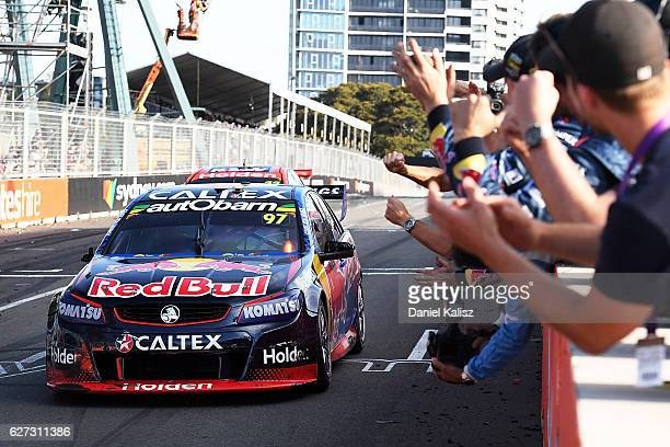 Shane Van Gisbergen driver of the Red Bull Racing Australia Holden Commodore VF crosses the finish line to finish in 3rd place and win the Supercars...