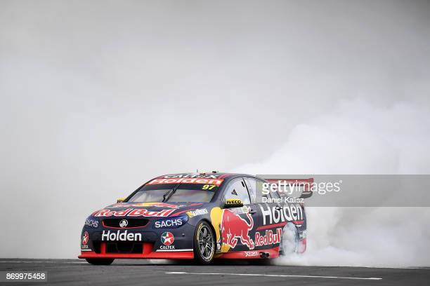 Shane Van Gisbergen drives the Red Bull Holden Racing Team Holden Commodore VF celebrates with a burnout after winning race 23 for the Auckland...