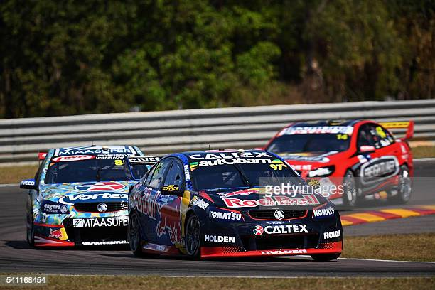 Shane Van Gisbergen drives the Red Bull Racing Australia Holden Commodore VF leads Craig Lowndes drives the TeamVortex Holden Commodore VF during...