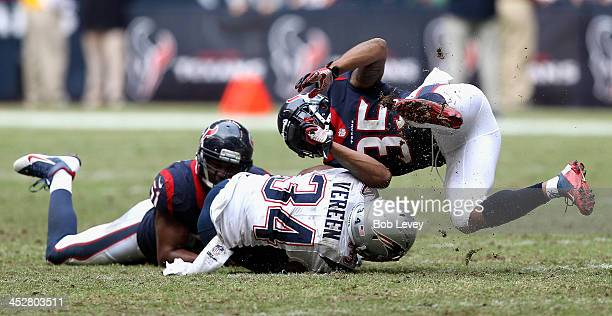 Shane Vereen of the New England Patriots takes a hit from Eddie Pleasant of the Houston Texans and Darryl Sharpton at Reliant Stadium on December 1...