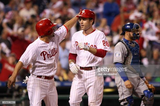 Shane Victorino and Chase Utley of the Philadelphia Phillies celebrate after they scored on a 2-run home run by Utley in the bottom of the sixth...