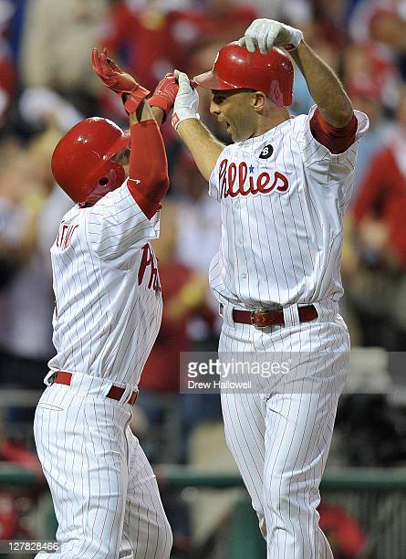 Shane Victorino and Raul Ibanez of the Philadelphia Phillies celebrate after a tworun home run by Ibanez in the sixth inning of Game One of the...