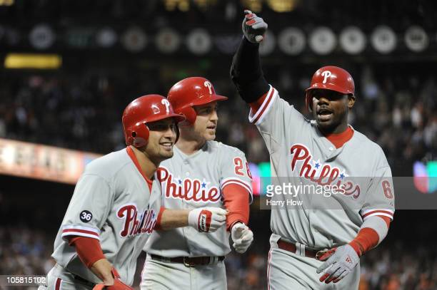 Shane Victorino Chase Utley and Ryan Howard of the Philadelphia Phillies celebrate after Victorino and Utley scored on a double by Placido Polanco...