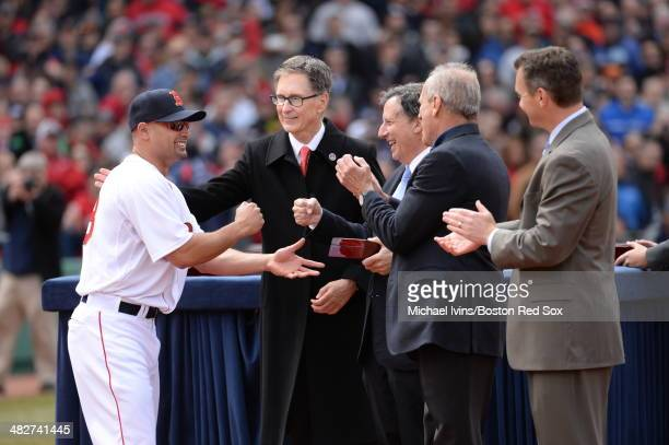 Shane Victorino of the Boston receives a championship ring from Principal Owner John W. Henry and Chairman Tom Werner during a ceremony honoring the...