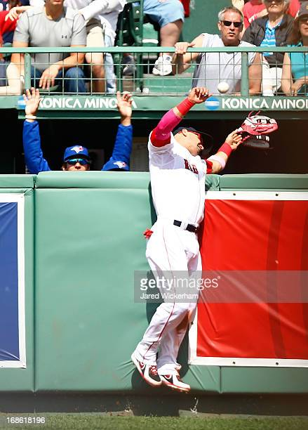 Shane Victorino of the Boston Red Sox hits the wall and loses his glove as the ball hit by Emilio Bonifacio of the Toronto Blue Jays goes over the...