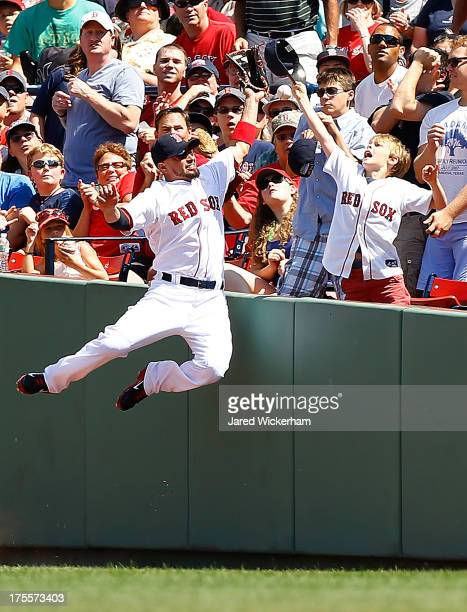 Shane Victorino of the Boston Red Sox leaps over the right field wall in foul territory while missing a pop fly in front of a young fan during the...