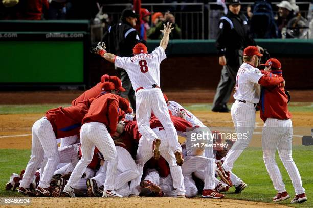 Shane Victorino of the Philadelphia Phillies dives on top of his teammates as they pile on top of closing pitcher Brad Lidge after they won 43 to win...