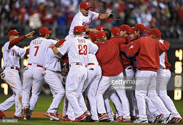 Shane Victorino of the Philadelphia Phillies jumps on top of his teammates after beating the Houston Astros 103 and winning the National League East...
