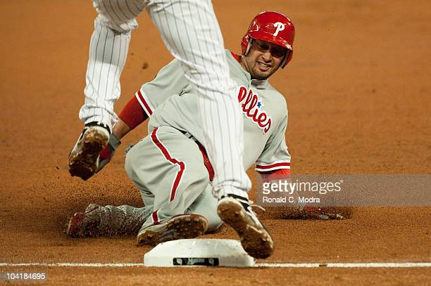 Shane Victorino of the Philadelphia Phillies slides into third base during a MLB game against the Florida Marlins at Sun Life Stadium on September 14...