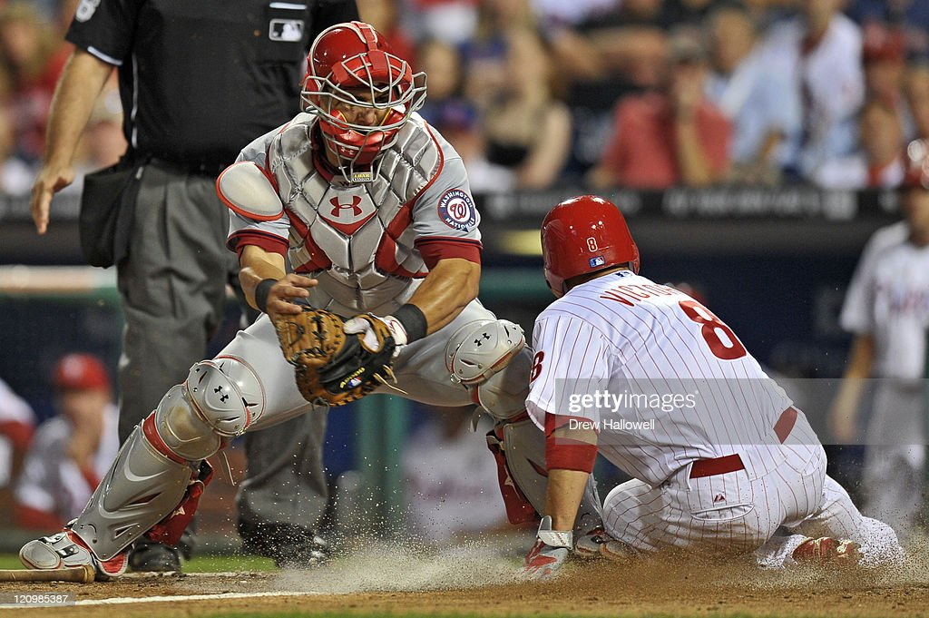 Shane Victorino #8 of the Philadelphia Phillies slides safe into home past the tag of Wilson Ramos #3 of the Washington Nationals at Citizens Bank Park on August 12, 2011 in Philadelphia, Pennsylvania. The Nationals won 4-2.