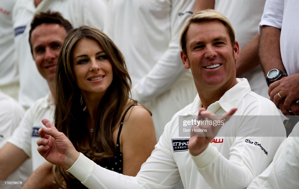 Shane Warne and Elizabeth Hurley look on prior to Shane Warne's Australia vs Michael Vaughan's England T20 match at Cirencester Cricket Club on June 09, 2013 in Cirencester, England.