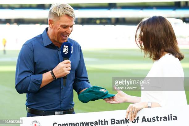 Shane Warne hands over his baggy green cap during the Big Bash League match between the Melbourne Stars and the Sydney Sixers at the Melbourne...