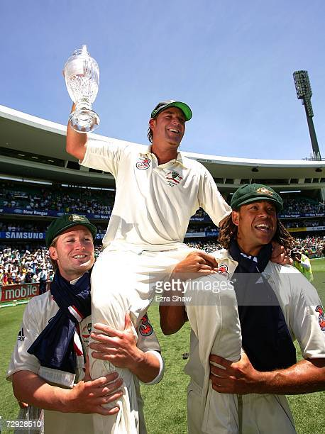 Shane Warne of Australia celebrates on the shoulders of Michael Clarke and Andrew Symonds with the Ashes trophy after winning the final test and...