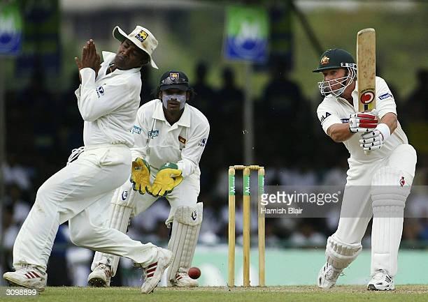 Shane Warne of Australia drives as Hashan Tillakaratne of Sri Lanka jumps clear during day one of the Second Test between Australia and Sri Lanka...