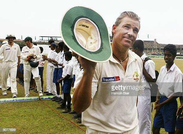 Shane Warne of Australia leaves the field at the end of the match after taking his 500th career wicket during day five of the First Test between...