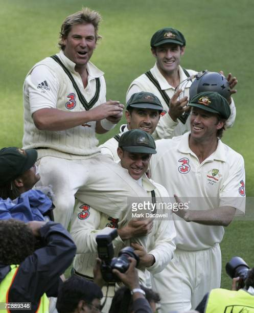 Shane Warne of Australia waves to the MCG crowd for the final time as he is chaired off by Andrew Symonds and Matthew Hayden after winning the fourth...
