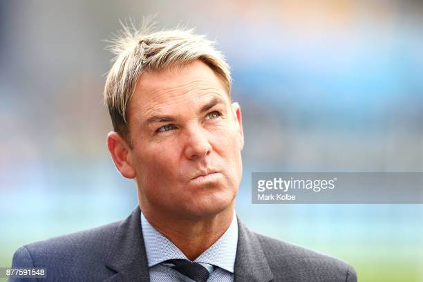 Shane Warne of the Channel Nine commentary team watches on as he waits to go to air before play day one of the First Test Match of the 2017/18 Ashes...