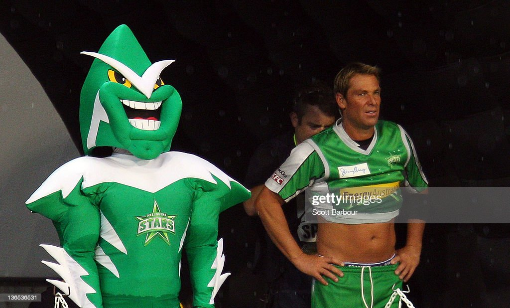 Shane Warne of the Stars is miked up for television as he stands next to the Stars mascot during the T20 Big Bash League match between the Melbourne Stars and the Melbourne Renegades at the Melbourne Cricket Ground on January 7, 2012 in Melbourne, Australia.
