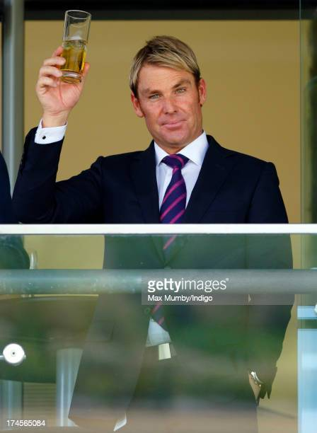 Shane Warne raises his glass whilst watching the racing as he and Elizabeth Hurley attend the Betfair Weekend featuring the King George VI and Queen...