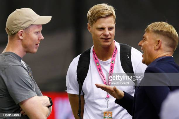 Shane Warne speaks with AFL Richmond Tigers player Jack Riewoldt and former AFL player Nick Riewoldt ahead of the Big Bash League match between the...
