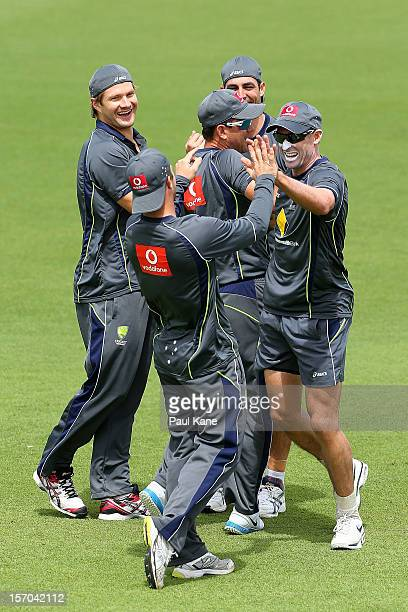 Shane Watson looks on as Matthew Wade and Michael Hussey celebrate winning a warm up game during an Australian training session at WACA on November...
