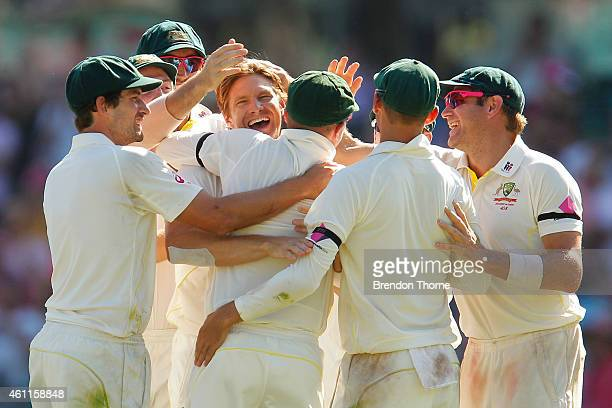Shane Watson of Australia celebrates with team mates after claiming the wicket of Suresh Raina of India during day three of the Fourth Test match...