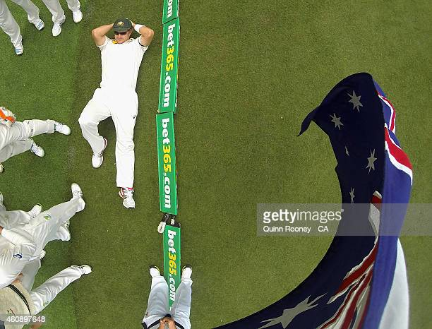 Shane Watson of Australia stretches up under the Australian flag during day five of the Third Test match between Australia and India at Melbourne...