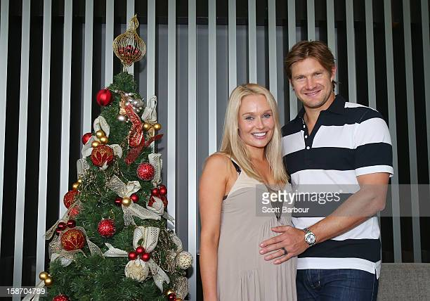 Shane Watson of Australia touches the stomach of his pregnant wife Lee Furlong as they pose next to a Christmas tree ahead of a Cricket Australia...