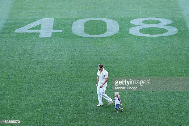 Shane Watson of Australia walks with son Will Watson after winning the match in front of the number 408 dedicated to the late Phillip Hughes during...