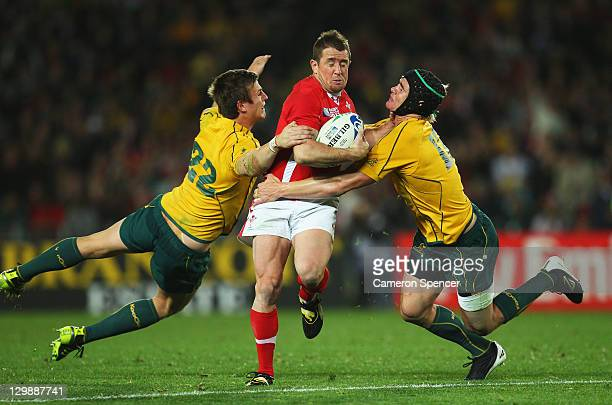 Shane Williams of Wales is tackled by Rob Horne and Berrick Barnes of the Wallabies during the 2011 IRB Rugby World Cup bronze final match between...