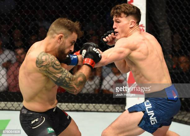 Shane Young of New Zealand punches Alexander Volkanovski of Australia in their catchweight bout during the UFC Fight Night event inside the Qudos...