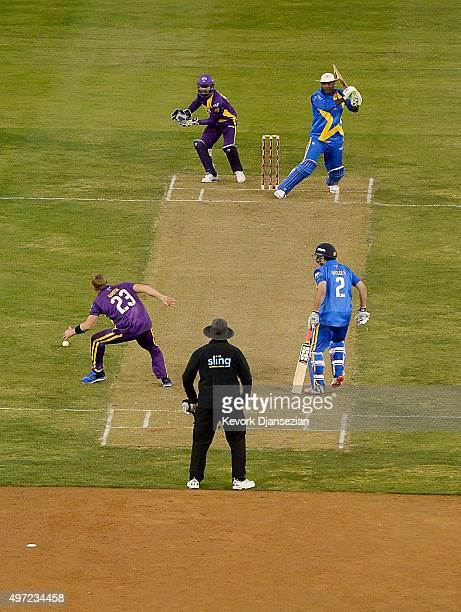 Shane's Warriors bowler Shane Warne attempts to catch the ball hit by Sachin's Blasters batsman Carl Hooper while Sachin's Blasters batsman Sourav...