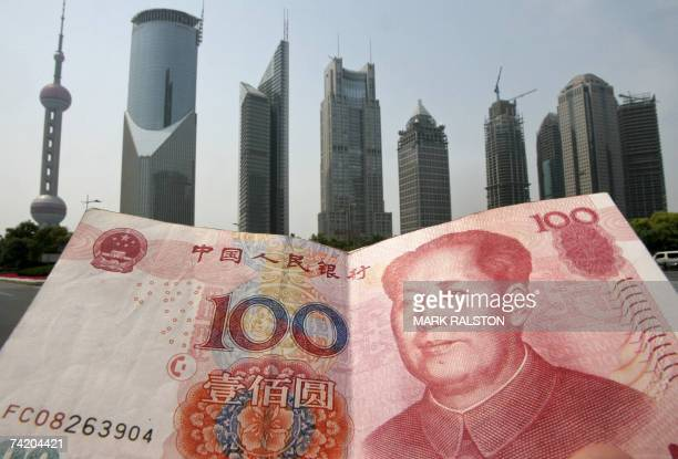 Chinese 100 renminbi note is held up in front of the Pudong financial district skyline in Shanghai, 21 May 2007. China recently said that it will...