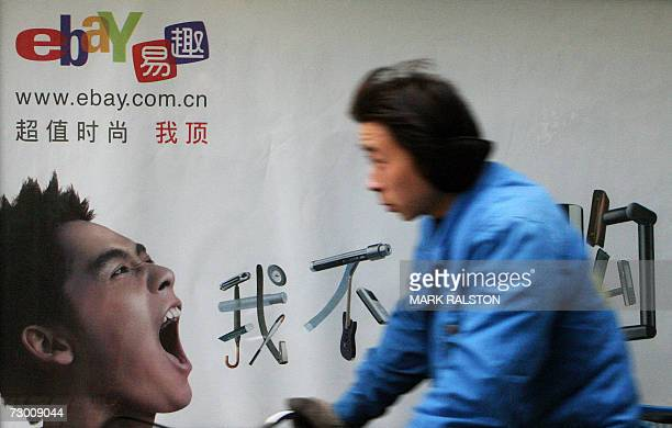 A Chinese man rides past a poster promoting the local version of the US online trading website EBay in Shanghai 16 January 2007 EBay which has helped...