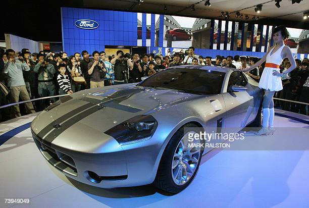 A Chinese model poses next to a Ford GT sports car on the opening day for the public of the Auto Shanghai exhibition 22 April 2007 Global automakers...