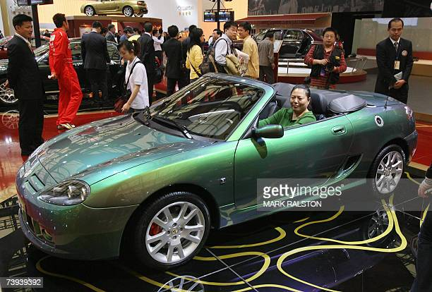 Chinese woman tries out an MG 7 convertible in the Nanjing Auto companies display at the Auto Shanghai exhibition, 21 April 2007. Nanjing Auto's MG...