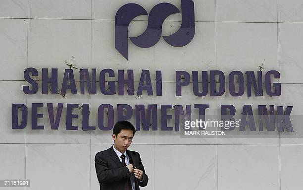 A customer leaves a branch of the Shanghai Pudong Development Bank in Shanghai 08 June 2006 The bank in which US banking giant Citigroup is a...