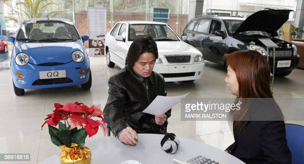 A customer looks at a sales contract at a dealership of China's largest car exporter Chery Automobile in Shanghai 22 February 2006 The company which...
