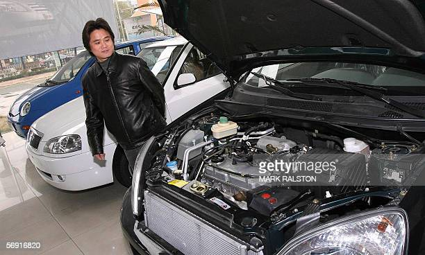 A customer looks at the engine of a SUV at a dealership of China's largest car exporter Chery Automobile in Shanghai 22 February 2006 The company...