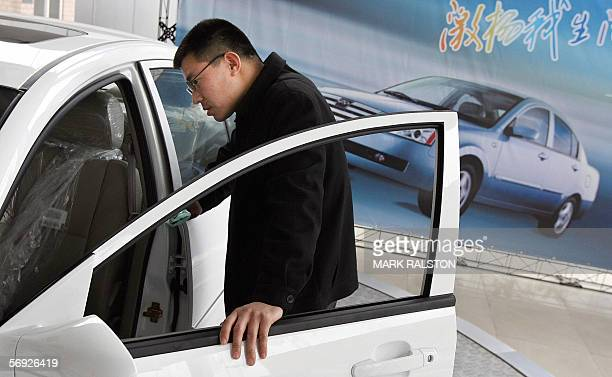 A customer looks at the interior of a sedan at a dealership of China's largest car exporter Chery Automobile in Shanghai 22 February 2006 The company...