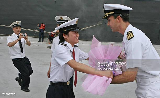 A female Chinese PLA navy officer presents the commander of the USS Blue Ridge Captain Jeffrey Bartkoski with a bouquet of flowers upon the ships...