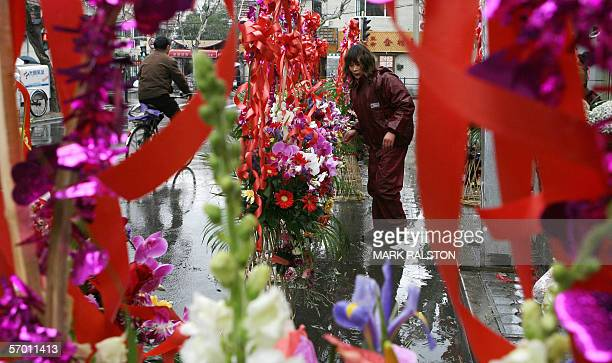 A florist prepares floral arrangements outside during a wet day in the old French concession area of Shanghai 28 February 2006 The baskets are...