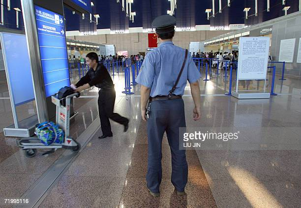 A security officers inspect the Pudong International Airport in Shanghai 26 September 2006 Extra police been deployed at Shanghai's airports and...
