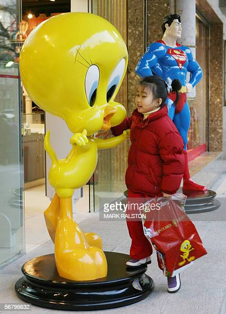 A young Chinese girl plays on a 'Tweety Bird' statue outside a newly opened Warner Brothers store on the Nanjing Road shopping street in Shanghai 09...