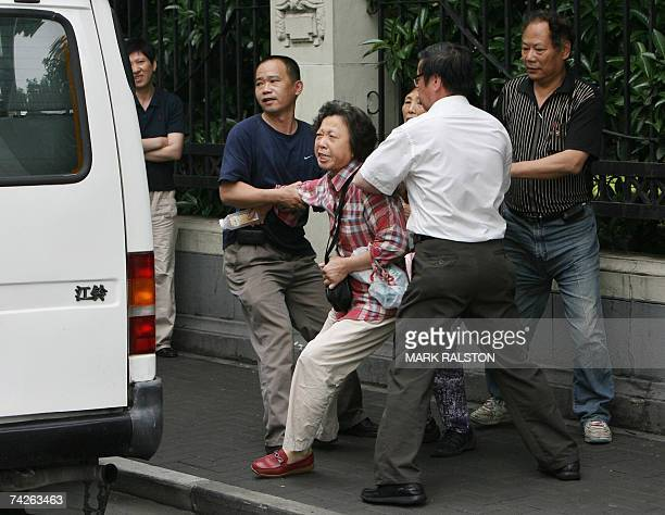 An elderly Chinese woman protesting over housing issues, is forced into a van after being detained by undercover police near the site of the...