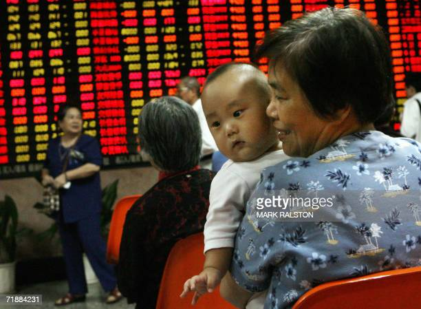 An elderly Chinese woman who spends her retirement as a day trader holds a friends grandson as she watches share prices at a security brokerage firm...