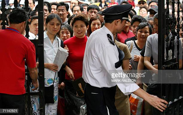 Anxious parents wait outside the school gate as their children sit the first of their college entrance exams at the historic Guangming high school...