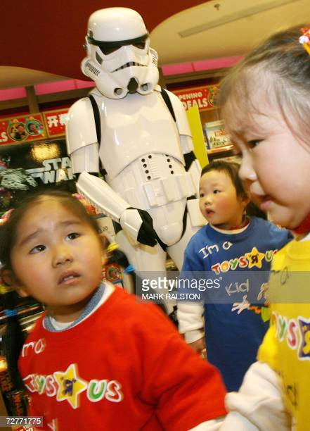 Chinese children pass a stormship trooper as they tour China's first Toys 'R' Us store which opened in Shanghai, 08 December 2006. Global retailing...