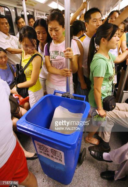 Chinese commuters look at blocks of ice placed in bins to help cool a crowded subway train as high temperatures continue in Shanghai 03 August 2006...